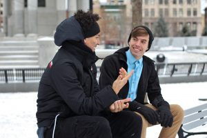 Conversation of two people sitting on a bench.