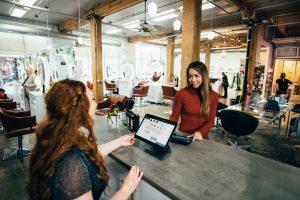"""Zwei Damen sitzen voreinander am Tisch. Kunde und Mitarbeiter, """"Beispiele gelungener verbaler Kommunikation"""""""