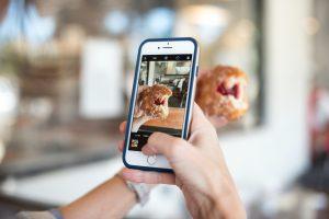 """Eine Hand hält ein Handy und filmt Gebäck. """"Visual Storytelling Trends"""""""