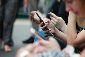"""Verschiedene Menschen sitzen mit ihren Smartphones. """"Beispiele für gelungene verbale Kommunikation""""."""