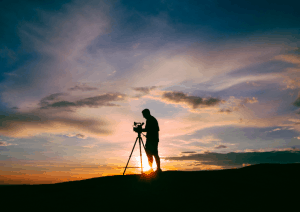 Silhouette Mann mit Kamera bei einem Sonnenaufgang.